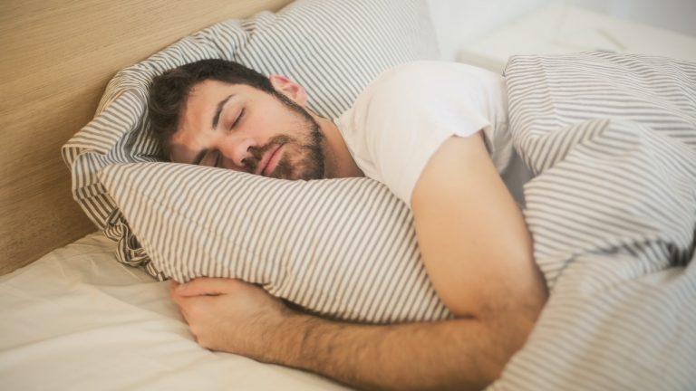 Mand sover i seng og krammer pude